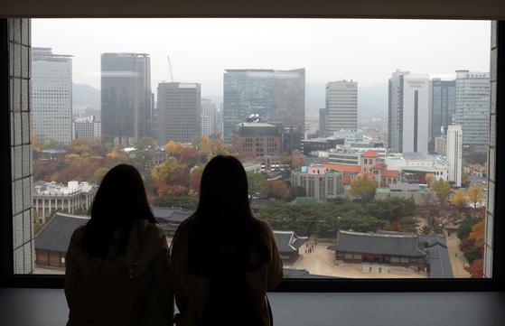 '미세먼지 비상저감조치'가 발령된 지난달 7일 서울 중구 정동전망대에서 관광객들이 창문 밖으로 단풍을 구경하고 있다. [뉴시스]