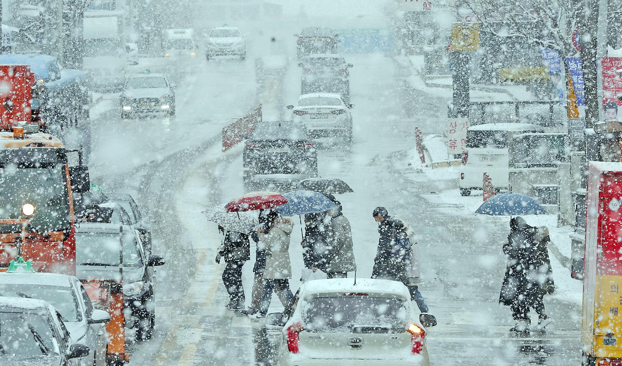 지난 11일 강원 춘천 도심 중앙로 거리에 많은 눈이 내려 차량들이 서행을 하고 있다. [연합뉴스]