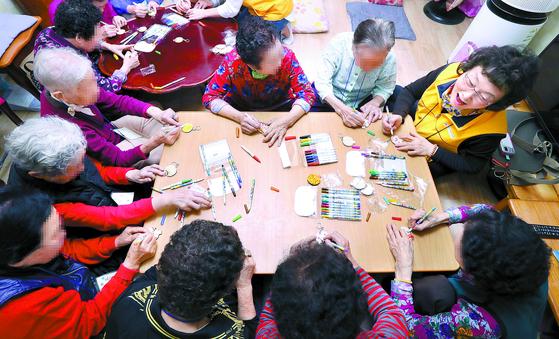 지난 10월 서울 성북구 장위동의 한 경로당에서 강사의 지도를 받으며 노인들이 치매 예방 교육 수업 중 하나인 열쇠고리 만들기를 하고 있다. [강정현 기자]