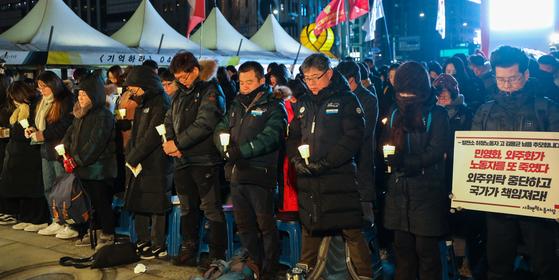 지난 15일 서울 광화문광장에서 열린 태안화력발전소 비정규직 사망 추모 문화제에서 참석자들이 고인을 향한 묵념을 하고 있다. [뉴스1]