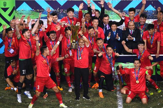 박항서 감독(가운데)이 15일(한국시간) 베트남 하노이의 미딩 국립경기장에서 2018 아세안축구연맹(AFF) 스즈키컵 우승 트로피를 들어 올리고 있다. [AFP=연합뉴스]