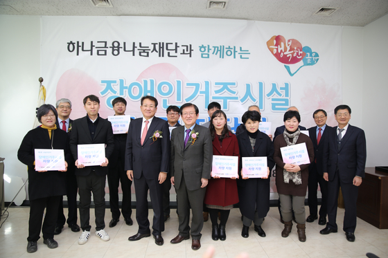 서상목 한국사회복지협의회장(왼쪽 네 번째)과 김한조 하나금융나눔재단 이사장(왼쪽 세 번째) 및 장애인거주시설 관계자 등이 차량 전달식 후 기념촬영을 하고 있다.