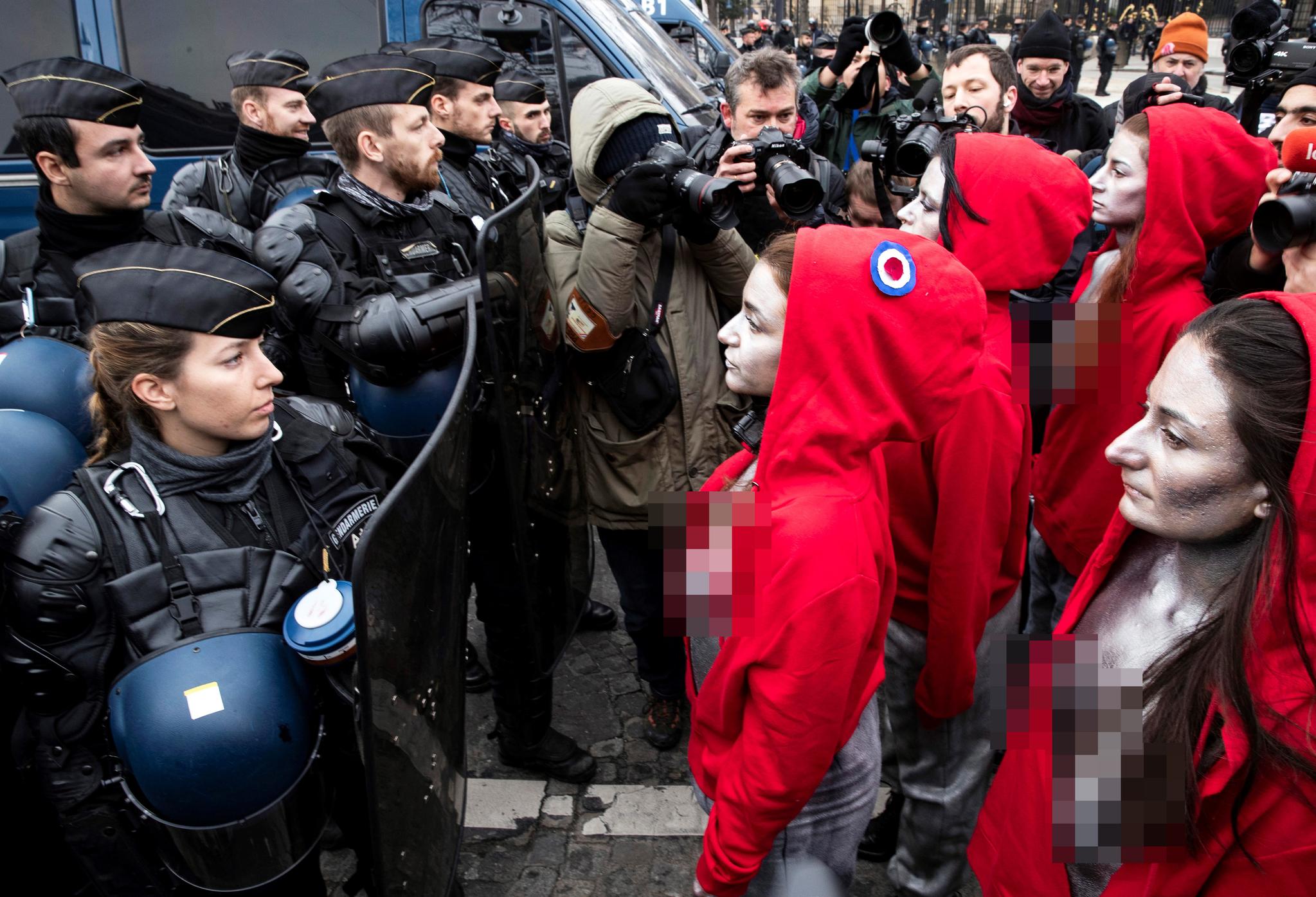 진압복을 입은 프랑스 파리 경찰들이 15일 파리에서 열린 '노란 조끼' 시위 현장에서 프랑스의 상징적인 마리안네 (Marianne) 인물 (자유여신상)을 상징하는 여성 시위대와 대치하고 있다. [EPA=연합뉴스]