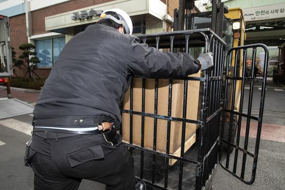 무장한 호송관이 생산된 금괴를 잠금장치가 있는 철제 상자에 옮겨 넣고 있다. 금괴는 특수차량으로 운반된다. 김현동 기자