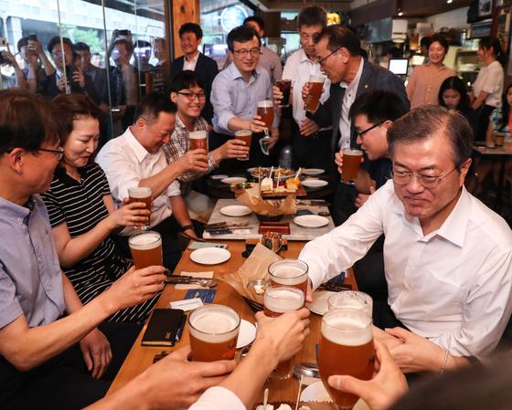문재인 대통령이 지난 7월 26일 오후 서울 광화문 인근 한 맥줏집에서 퇴근길 시민들과 만나 건배하고 있다. 이 날 행사는 대통령 후보 시절 약속한 '퇴근길 국민과의 대화 일환'으로 열렸다. [연합뉴스]