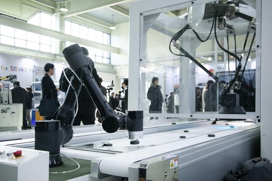 5G 머신 비전이 유리방에서 찍힌 사진을 토대로 AI가 판단해 보내온 불량 정보를 받아 불량품을 골라 내고 있다. [사진 SK텔레콤]