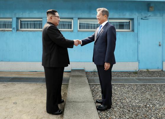 문재인 대통령과 북한 김정은 국무위원장이 4월 27일 판문점에서 군사분계선을 사이에 두고 악수하는 모습. 연합뉴스