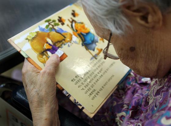 어느 실버 케어 센터에서 돋보기를 쓰고도 얼굴 가까이 동화책을 가져와 읽는 노인의 모습. 노안, 당뇨, 백내장 등으로 시력에 어려움을 겪게 되는 시니어가 늘자 큰 활자 책 시장이 블루오션으로 떠올랐다. [중앙포토]