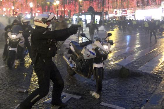 파리 샹젤리제 거리 인근에서 한 경찰관이 시위대를 향해 권총을 겨누고 있다. [AP=연합뉴스]