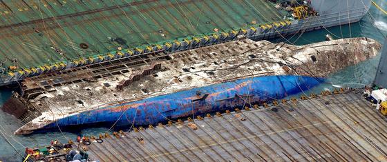 지난해 3월 세월호 침몰 해역인 전남 진도군 동거차도 앞바다에서 중국 인양업체인 상하이샐비지의 재킹바지선 두척이 세월호 인양작업을 진행하고 있는 가운데 세월호가 모습을 드러내고 있다. 김상선 기자