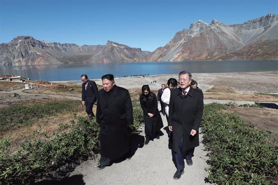 문재인 대통령(오른쪽)과 김정숙 여사가 9월 20일 김정은 국무위원장 내외와 백두산 천지를 산책하고 있다.