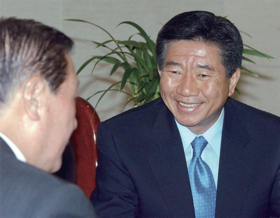 2002년 당시 노무현 민주당 대통령후보가 여의도당사에서 김원기 정치고문에게서 당무회의 결과를 보고 받으며 웃고 있다.