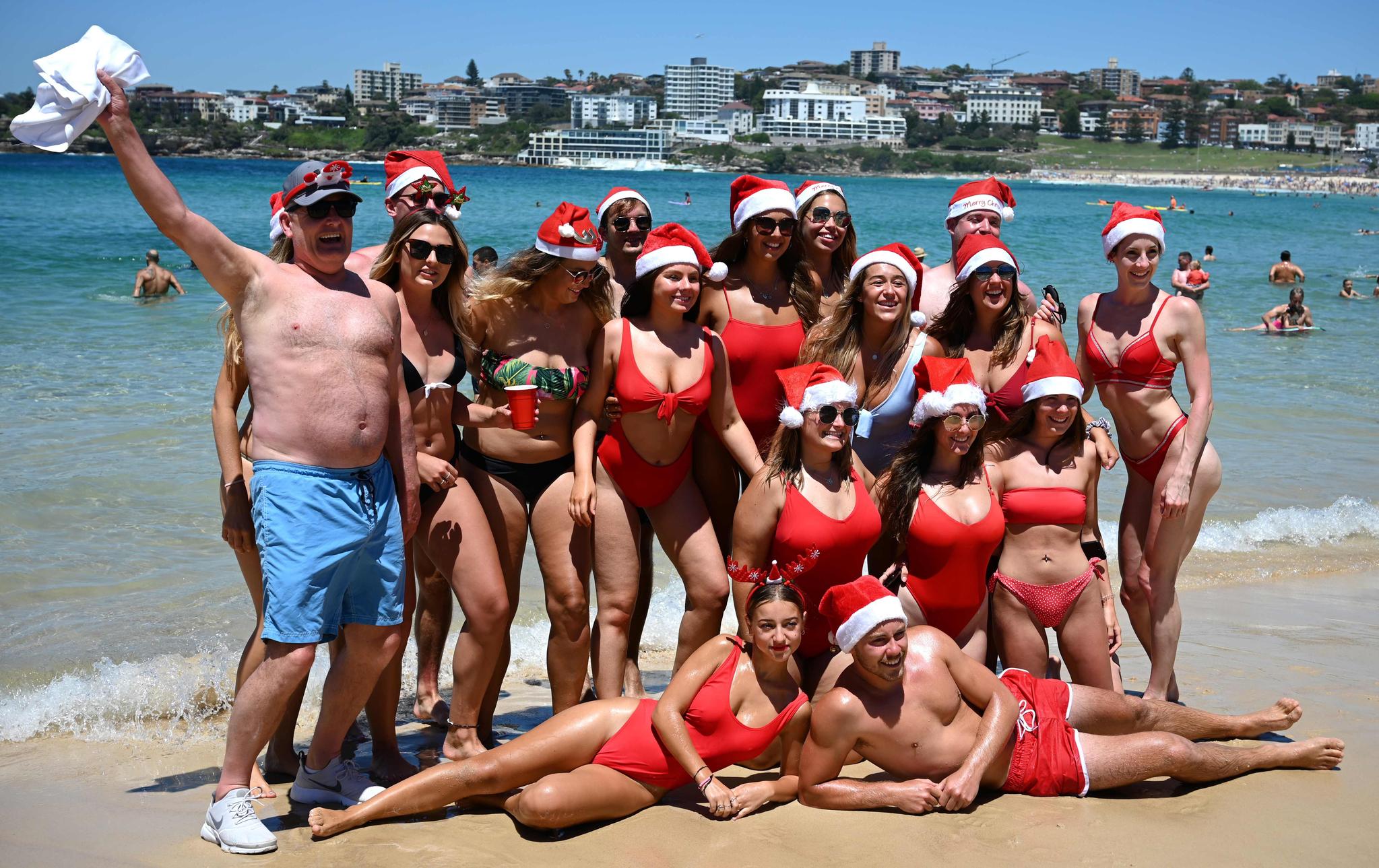 관광객들이 25일(현지시간) 호주 시드니 본다이 비치에서 산타 모자와 비키니 수영복을 입고 기념촬영하고 있다. [AFP=연합뉴스]