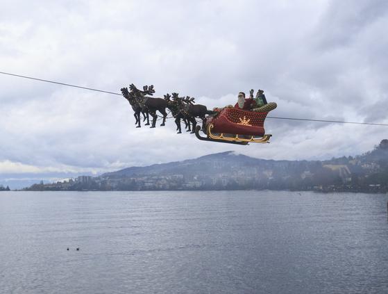 지난 22일 스위스 서부 몽트뢰의 레만 호수 위에 날고 있는 산타클로스와 썰매. 몽트뢰에는 스위스 최대의 장터가 열린다.[신화사=연합]