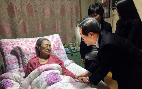제1회 '바른 의인상' 수상자인 김복동 할머니(왼쪽)를 방문한 공익사단법인 '정'의 김재홍 이사장(서울디지털대학교 총장)이 수상을 통보하며 할머니 손을 잡고 위로하고 있다. [사진 법무법인 바른]