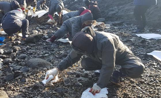 전날 기름 유출 사고가 발생한 충남 홍성군 서부면 죽도에서 주민들이 26일 흡착포를 이용해 방제작업을 하고 있다. [연합뉴스]