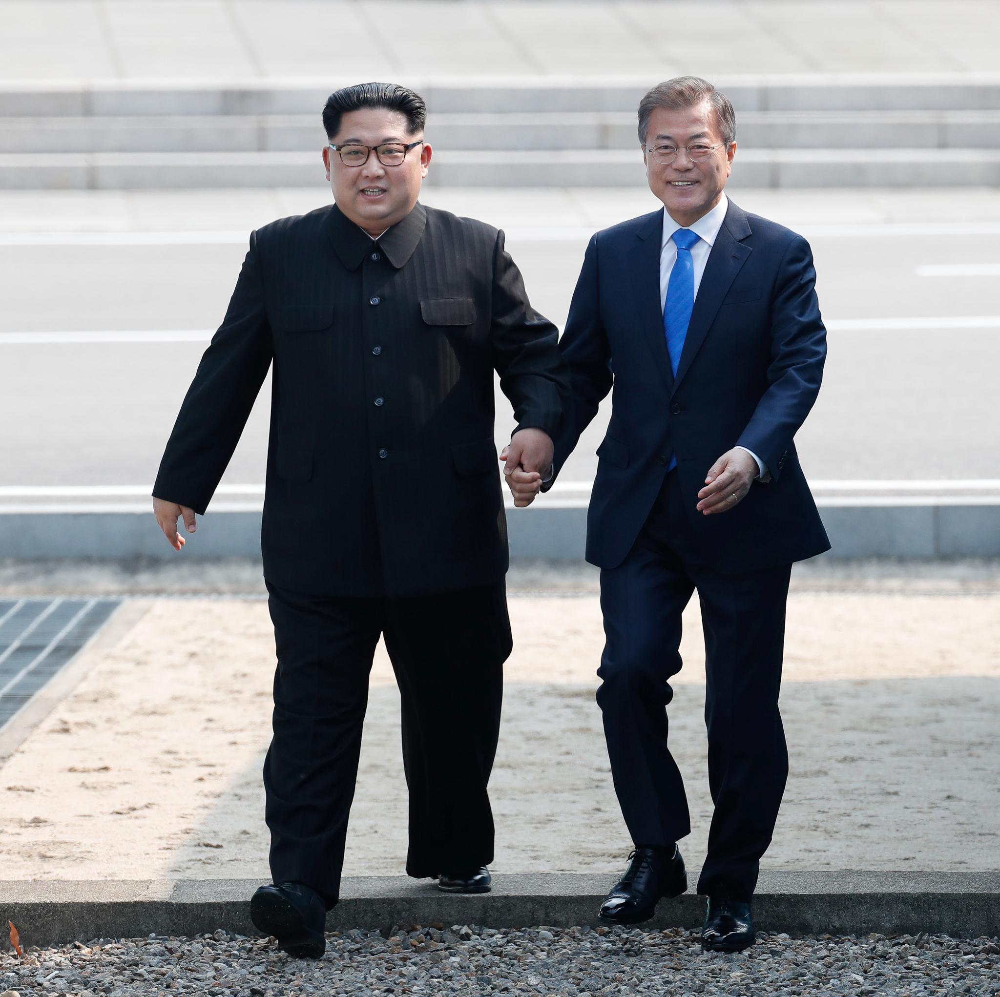 역사적인 남북 정상의 첫 만남. 문재인 대통령과 김정은 국무위원장이 함께 손을 잡고 판문점 군사분계선을 넘고 있다. 사진공동취재단