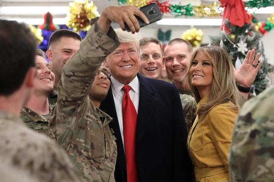 26일(현지시간) 이라크 바그다드의 미공군기지를 방문한 트럼프 대통령과 멜라니아 여사가 군장병들과 '셀카'를 찍고 있다. [로이터=연합뉴스]