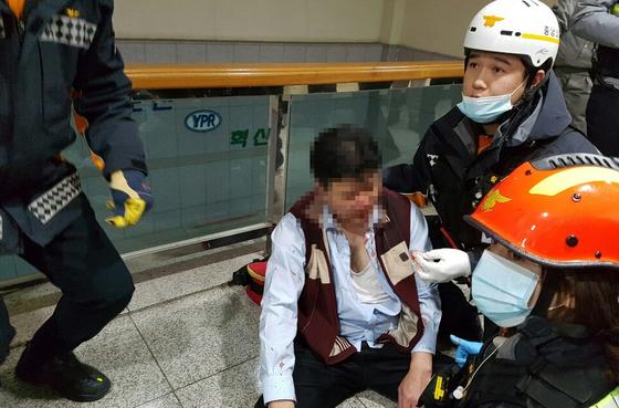 지난달 22일 금속노조 유성기업지회 노조원들에게 폭행당한 유성기업 임원이 출동한 119구급대원들에게 응급치료를 받고 있다. [사진 유성기업]