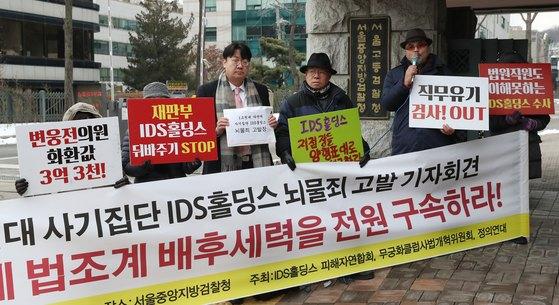 IDS홀딩스 피해자연합회 회원들이 지난해 12월 서울 서초구 서울중앙지방법원 앞에서 'IDS홀딩스 대표 김성훈 뇌물죄 고발 기자회견'을 하고 있다. [뉴스1]