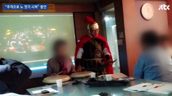 JTBC 뉴스룸은 27일 최수봉 건국대 충주병원 교수가 자신이 차린 수일개발 직원들에게 로마 시대를 배경으로 한 영화 '벤허'에 등장하는 노예들의 흉내를 내라고 했다고 보도했다. 최 교수는 직접 로마 집정관 복장을 하고 나와 직원들에 구호에 맞춰 노를 젓는 시늉을 하라고 시켰다는 게 여러 직원들의 주장이다. [JTBC 뉴스룸 캡처]