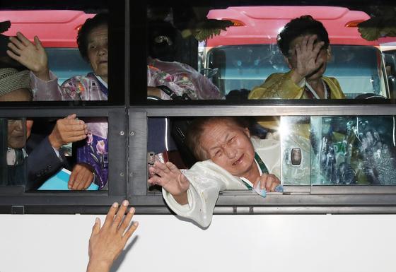 지난 8월 21차 이산가족 상봉행사 2회차 마지막날인 26일, 북한 금강산호텔에서 열린 작별상봉 및 공동중식을 마치고 버스에 오른 북측 가족들이 남측 가족들과 헤어지며 눈물을 흘리고 있다.[연합뉴스]
