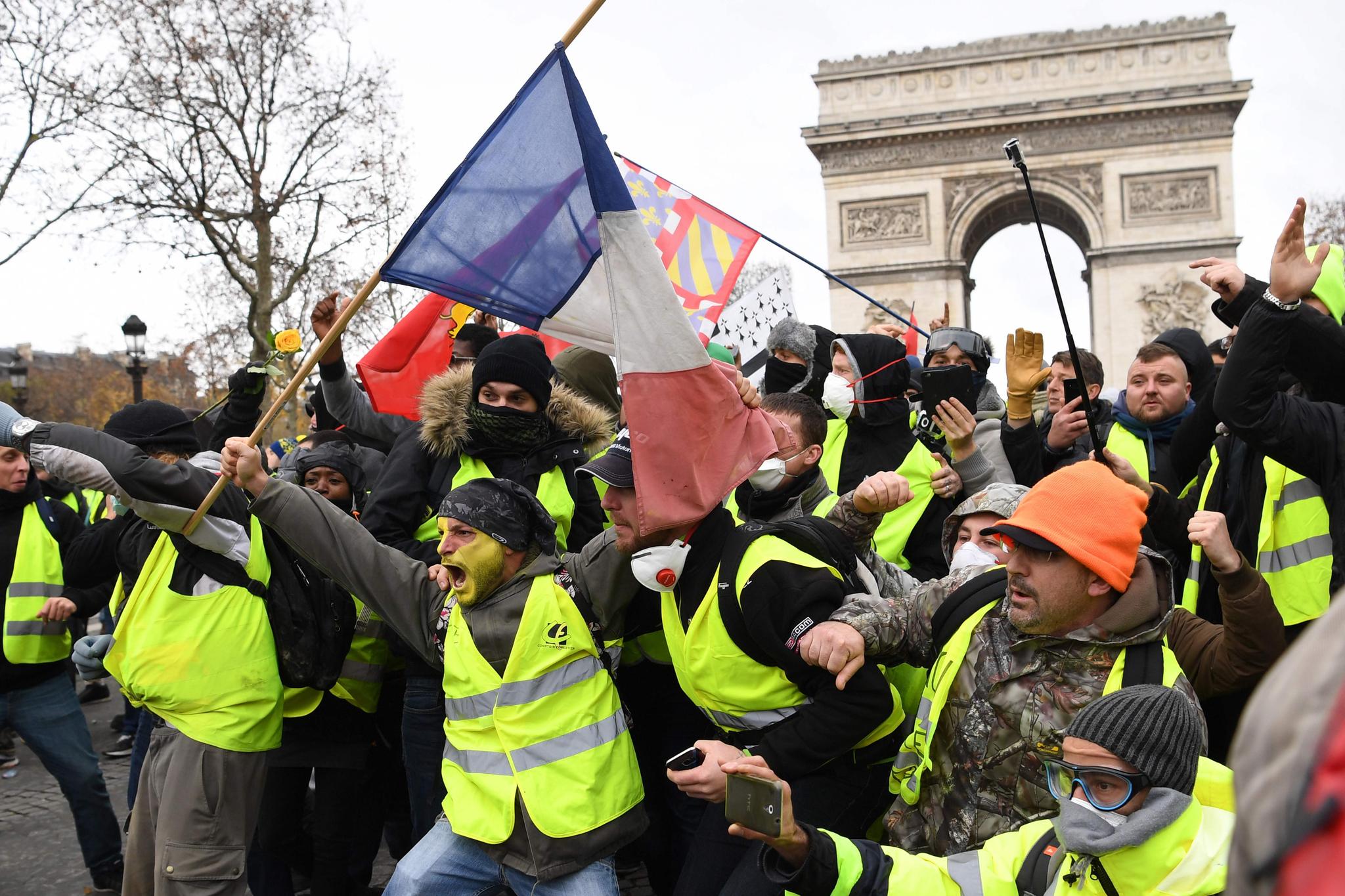12월 8일 노란조끼 시위대가 파리 개선문 앞에서 세금 인상 등에 반대하는 시위를 하고 있다. 마크롱 대통령은 12월 11일 세금인상 등을 철회하는 대국민 담화를 발표했다. [AFP=연합뉴스]
