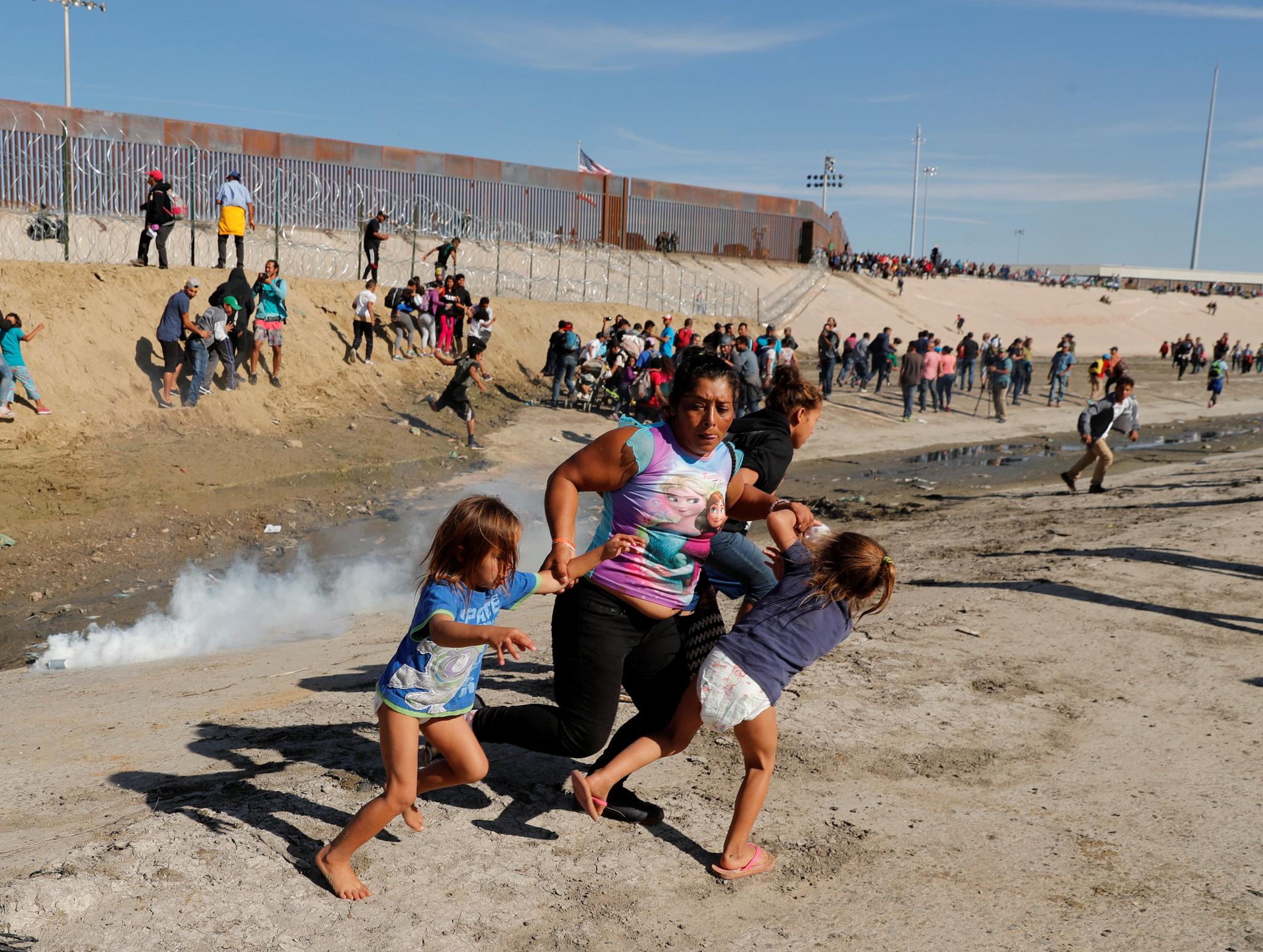 11월 25일 온두라스에서 온 마리아 릴라 메자 카스트로가 멕시코 티후아나 국경에서 최루탄을 피해 두 딸과 도망치고 있다. [로이터=연합뉴스]