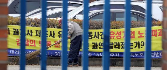 지난 5일 충남 아산시 유성기업에서 한 근로자가 노조 측이 걸어놓은 현수막 앞을 청소하고 있다. 대법원은 이 날 유성기업 측의 노조 탄압으로 정신질환이 생긴 노동자에 대해 '업무상 재해'를 인정했다. [뉴스1]