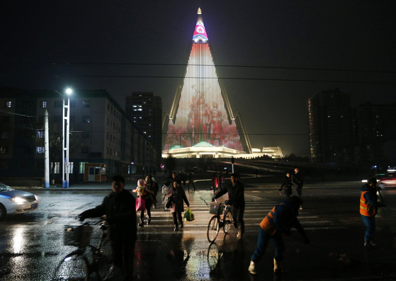 평양 시민들이 지난 18일 LED 조명으로 빛나는 류경호텔 앞을 지나고 있다. [AP=연합뉴스]