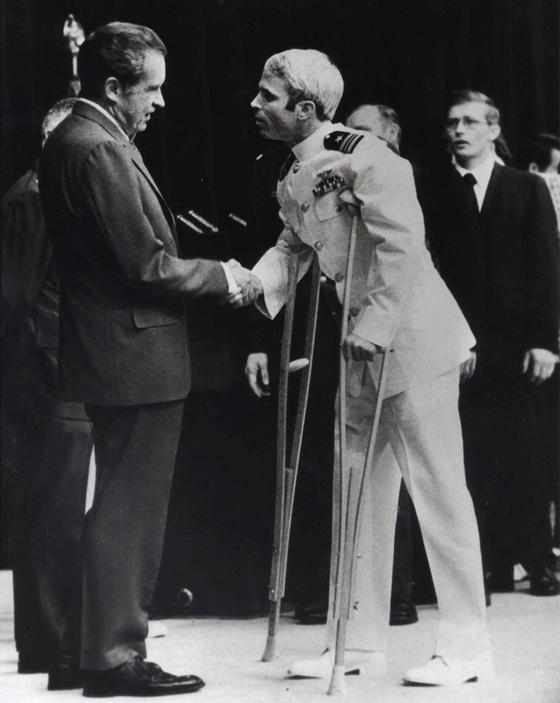 1973년 5월 워싱턴에서 열린 베트남전쟁 포로귀환 행사에서 목발을 짚은 존 매케인(오른쪽)이 리차드 닉슨 전 대통령과 악수하고 있다. [AP=연합뉴스]