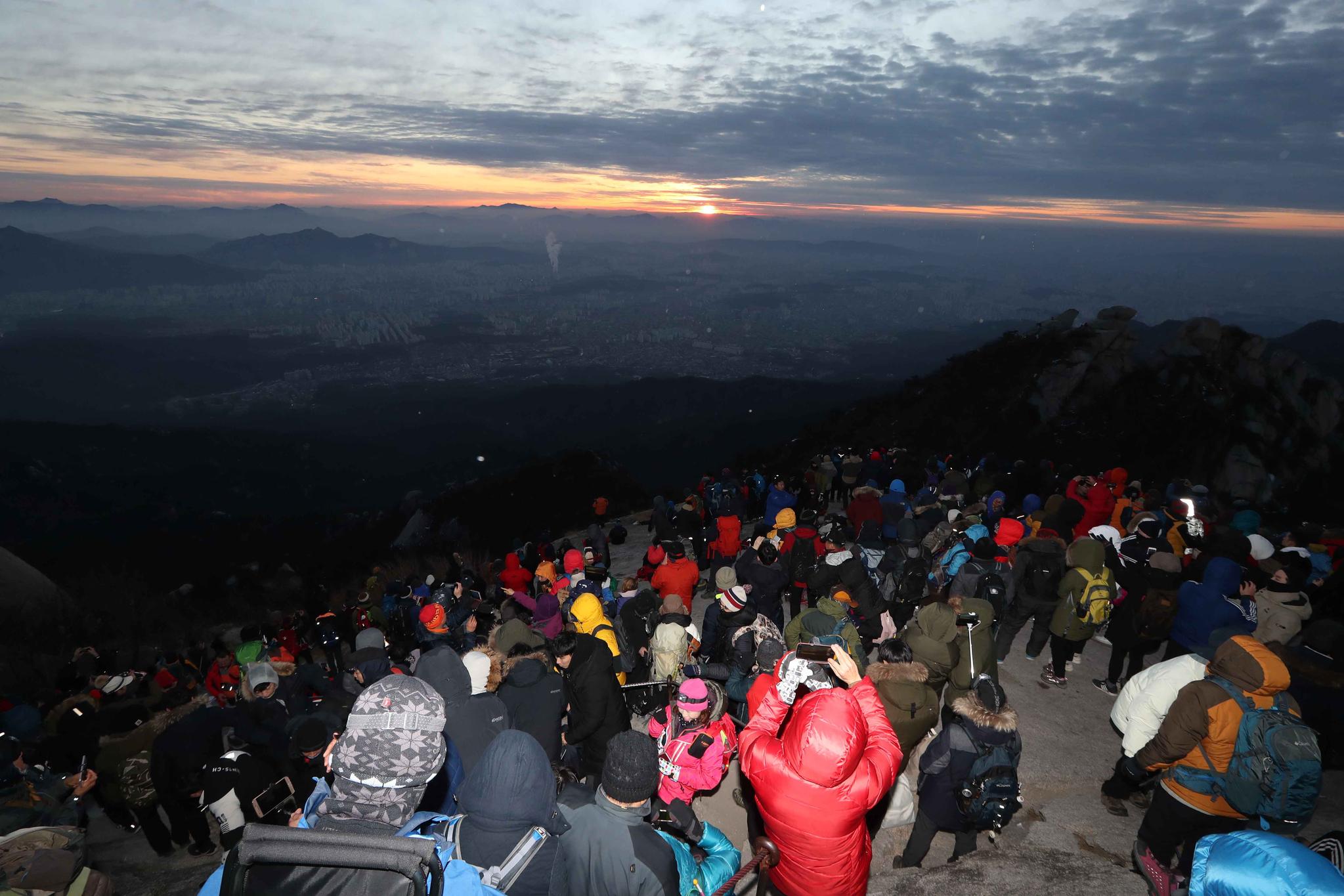새해 첫 날인 1일 등산객들이 북한산 백운대 정상에서 해돋이를 지켜보고 있다. 국립공원 북한산 우이분소는 이날 백운대에 1000 여명이 몰렸다고 밝혔다. 김상선 기자