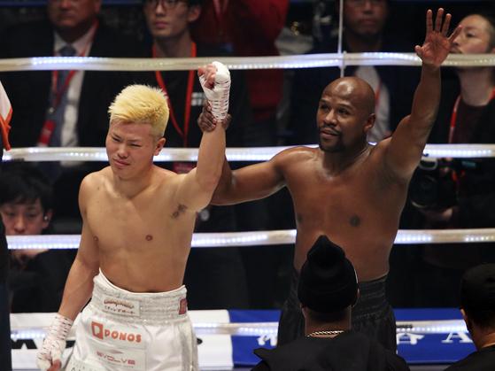 경기에서 승리한 메이웨더가 나스카와의 손을 들어주고 있다. 나스카와는 분한 마음에 눈물을 펑펑 쏟았다. [연합뉴스]