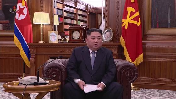 이례적으로 소파에 앉아 신년사 발표하는 김정은 국무위원장. 뒤로 탁상시계가 자정 0시 5분을 가리키고 있다. [연합뉴스]
