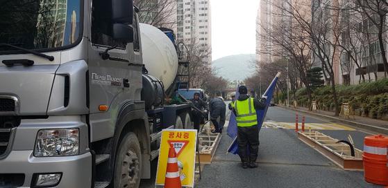 지난달 21일 LG메트로시티아파트 관통 도로 입구에 차량 차단기 설치가 진행 중이다. [이은지 기자]