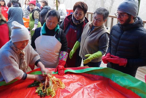 정관 스님이 배추김치 버무리는 방법을 설명하고 있다. 박광희 김치 명인(왼쪽 둘째), 한식 명장 조희숙 셰프(넷째)와 한 외국인 남자가 지켜보고 있다.