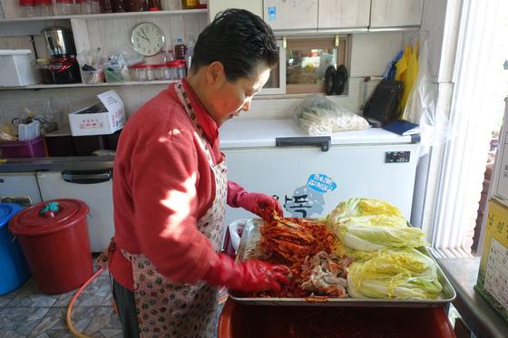 '옥이네밥상' 주인 김옥이씨가 돼지고기김치에 소를 넣고 있다.