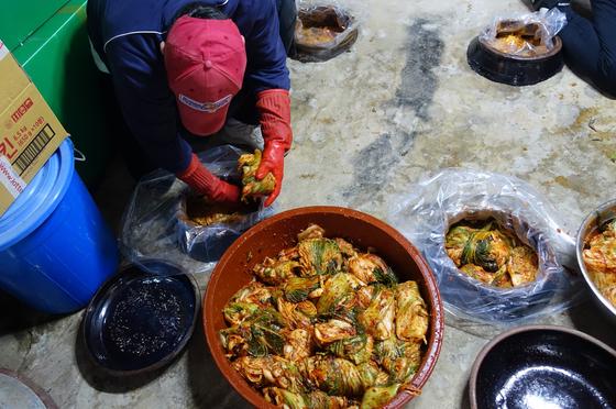 완성된 배추김치는 정관 스님의 김치 곳간으로 옮겨 땅에 묻은 6개의 독에 저장한다. 요리 배우는 젊은이가 김치를 쟁이고 있다.