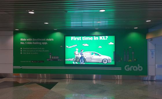 쿠알라룸푸르 공항에 도착하자마자 승객들을 맞이하는 그랩 광고판. 그랩은 말레이시아 정부의 규제 완화 정책에 힘입어 글로벌 유니콘으로 성장했다. 그랩의 성공에 영감을 받은 많은 청년들이 말레이시아에서 창업에 뛰어들고 있다. 김경진 기자