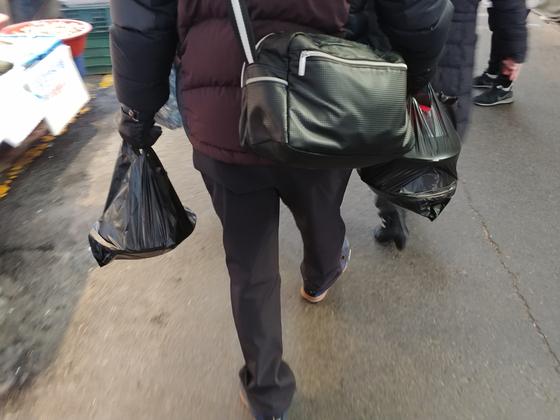 6일 낮 망원시장에서 장을 본 시민들이 손에 검정색 비닐봉지를 들고 있다 김정연 기자.