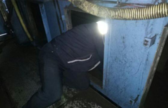 컨베이어 운전원은 컨베이어 벨트를 둘러싸고 있는 네모난 철제 구멍으로 몸을 집어넣고 안쪽에 이물질이 끼이진 않았는지 확인한다. [태안화력대책위원회 제공]