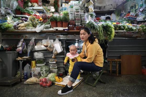 자신의 아기를 돌보고 있는 중국 여성 상인의 모습. [EPA=연합뉴스]