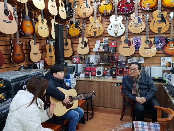 손창기(66)씨와 새 기타를 산 어린 손님이 이야기를 나누고 있다. [임성빈 기자]