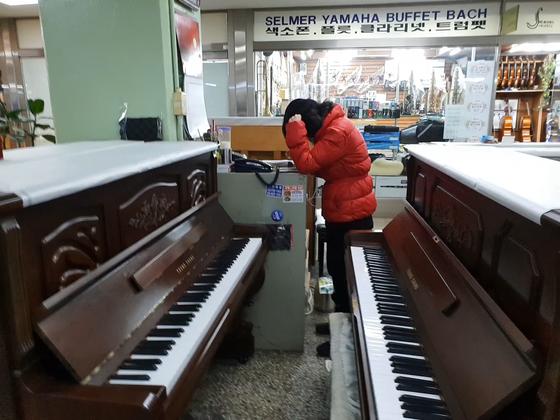 중고 피아노를 판매하는 오영미(61)씨가 혼자 가게를 지키며 전화 상담을 하고 있다. [임성빈 기자]