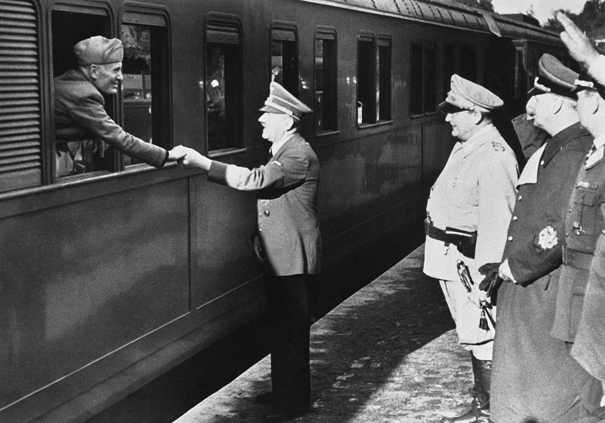 아돌프 히틀러 독일 수상(가운데)이 1944년 8월10일 독일에서 회의를 마치고 열차편으로 떠나는 이탈리아 독재자 베니토 무솔리니를 배웅하고 있다. 같은 해 7월 20일 암살 시도로 오른손을 다친 그는 왼손으로 무솔리니와 악수했다. [AP=연합뉴스]