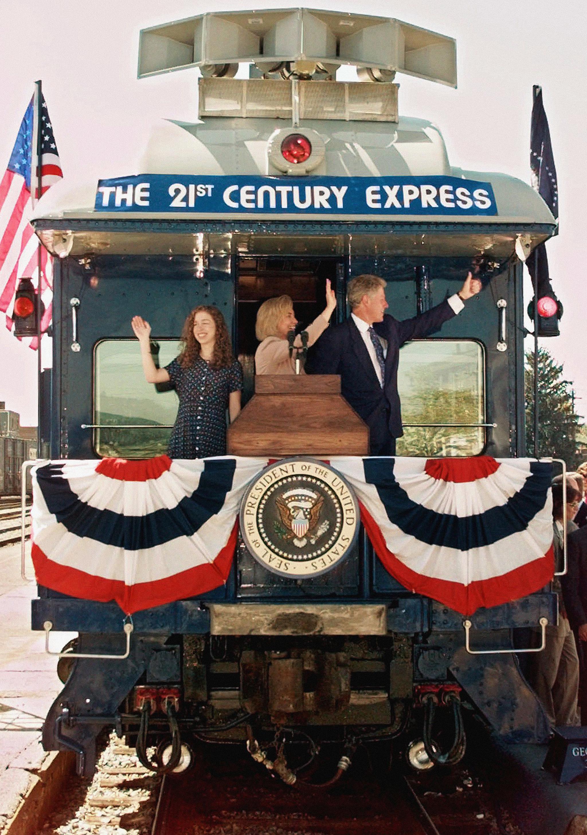 미국 빌 클린턴 대통령이 1996년 8월25일 부인 힐러리 여사와 딸 첼시와 함께 시카고에서 열리는 민주당 전당대회 참석을 위해 서버지니아주 헌팅턴 을 출발하며 열차에서 군중들에게 손을 흔들고 있다.[AP=연합뉴스]