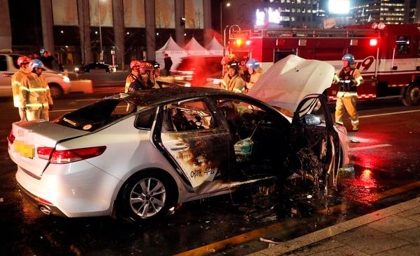 9일 오후 광화문대로에서 소방관들이 화재가 난 택시를 진화하고 있다. [연합뉴스]