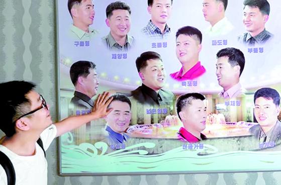 중국 스타트업 채널 SAO의 유튜버가 평양 문수몰놀이장 이발소에서 헤어스타일 사진을 보고 있다. [유튜브 캡처]