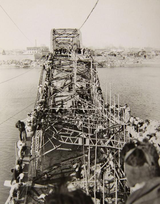 유엔군이 후퇴하자 부서진 대동강 철교를 건너 피난길에 오르는 평양시민들. 통일 꿈이 좌절된 모습을 담은 유명한 사진이다. [중앙포토]
