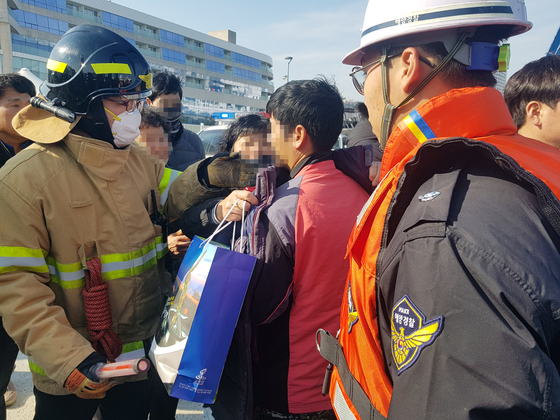 11일 오전 경남 통영 욕지도 해상에서 전복 사고가 난 낚시어선 '무적호'에서 구조된 한 낚시객이 가족을 만나 외투를 건네받고 있다. [연합뉴스]